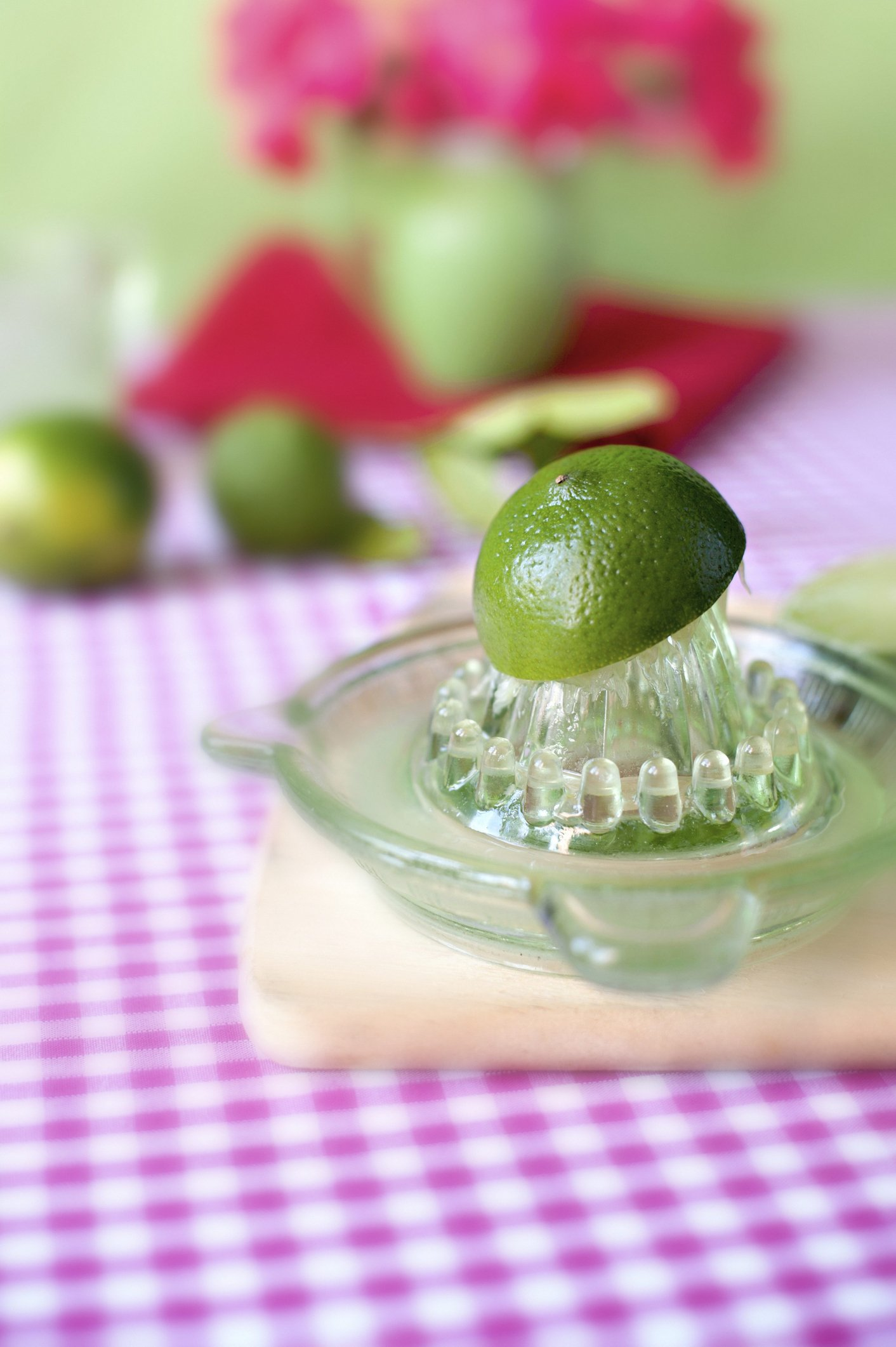 Fresh limes on a red and white gingham cloth being hand juiced in a vintage green glass juicer. | Photo: Getty Images