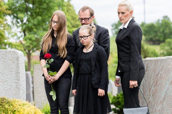une famille en deuil dans un cimetière   Source : Shutterstock
