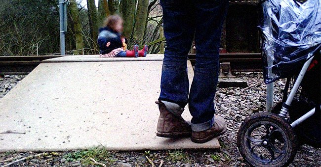 A parent looking on as their toddler sits on a railway crossing. │Source: twitter.com/WalesOnline
