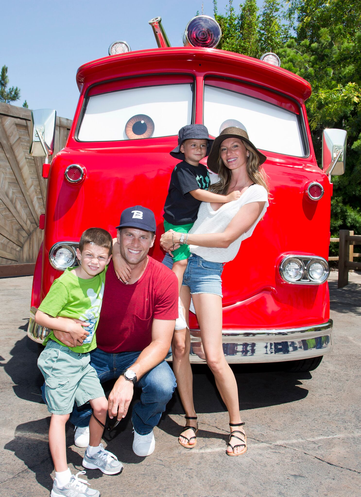 Tom Brady, his son Jack, 5, Gisele Bundchen, and their son Benjamin, 3, pose with Red the Fire Truck at Cars Land at Disney California Adventure park July 2, 2013  | Getty Images