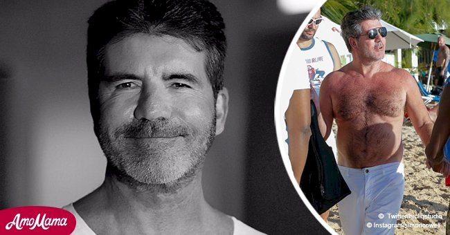 Simon Cowell flashes his belly on camera during a pre-Christmas day on the beach