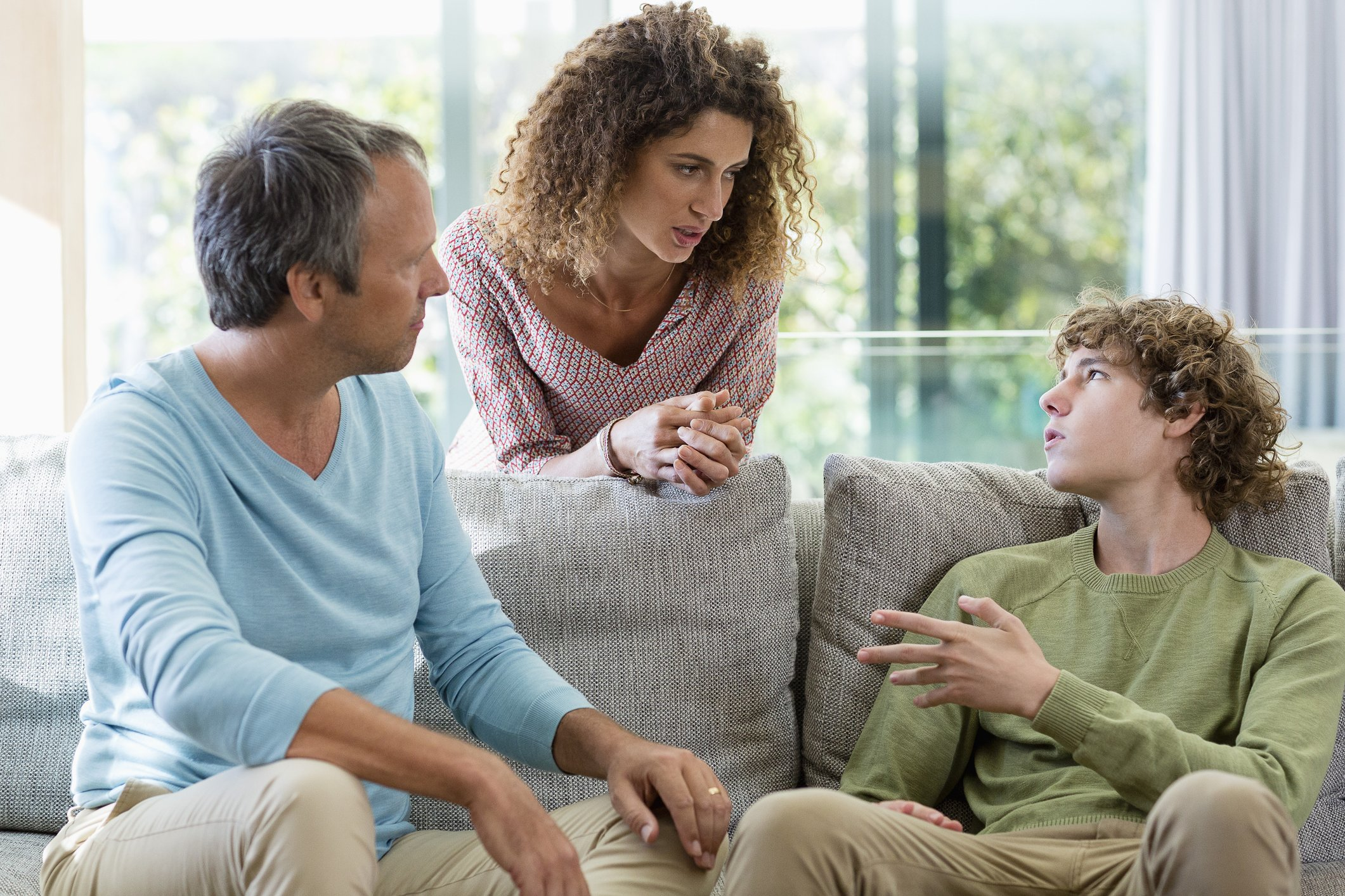 Parents talk to their teen son in the living room | Photo: Getty Images