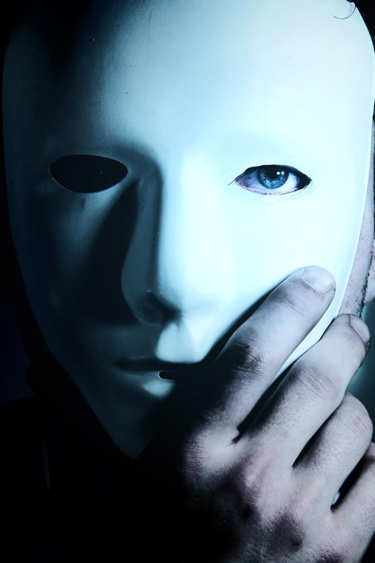 Pictured - A man with blue eyes wearing a mask with his hand holding it | Source: Pixabay