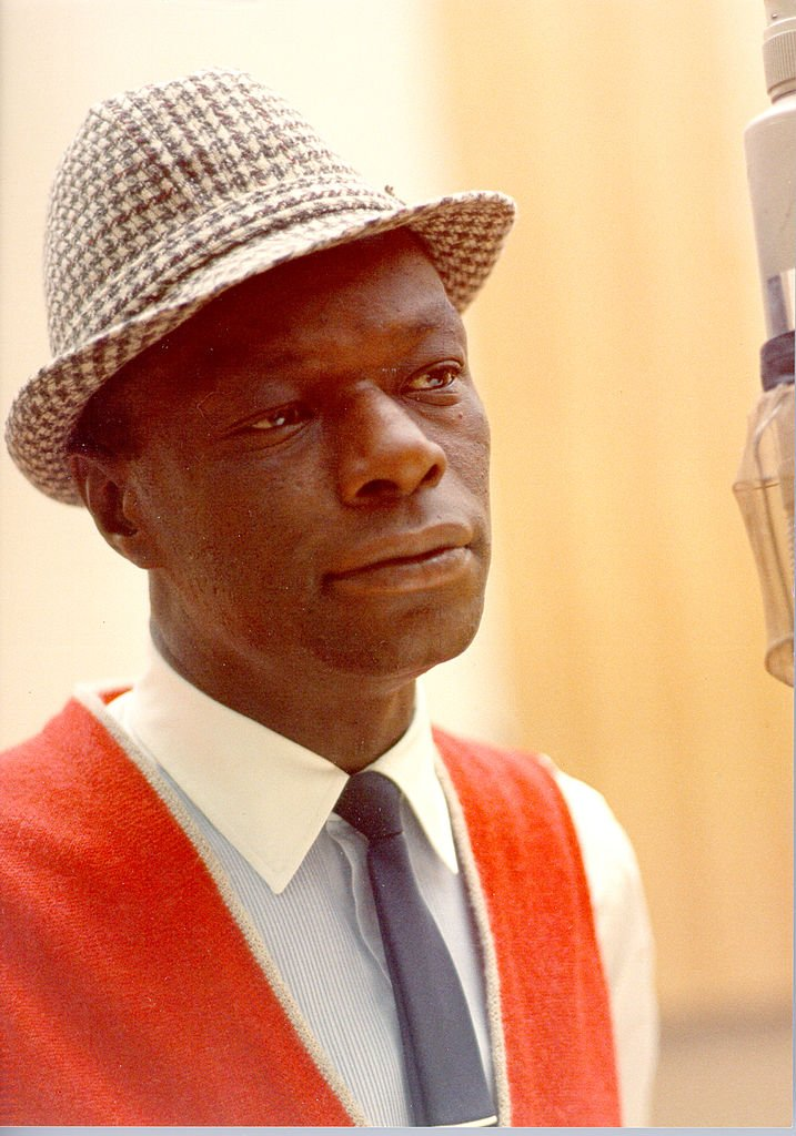 """Singer Nat """"King"""" Cole records during a session at Capitol Recording Studios, circa 1964. 