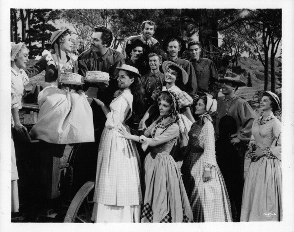 Nancey Kilgas, Jane Powell, Betty Carr, Ruta Kilmonis, Julie Newmeyer, Virginia Gibson and Norma Doggett as the seven brides and Howard Keel, Tommy Rall, Matt Mattox, Russ Tamblyn, Marc Platt, Jacques d Amboise and Jeff Richards as the seven brothers in a scene from the film 'Seven Brides For Seven Brothers', 1954 | Photo: Getty Images