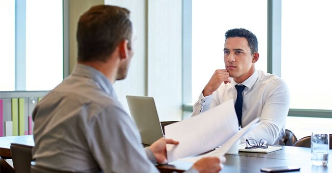 Photo of two men having a conversation in an office | Photo: Shutterstock.com