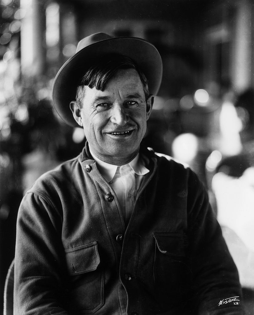 Portrait of American entertainer Will Rogers (1879-1935) sitting and smiling. He wears a hat and an overshirt. | Photo: Getty Images