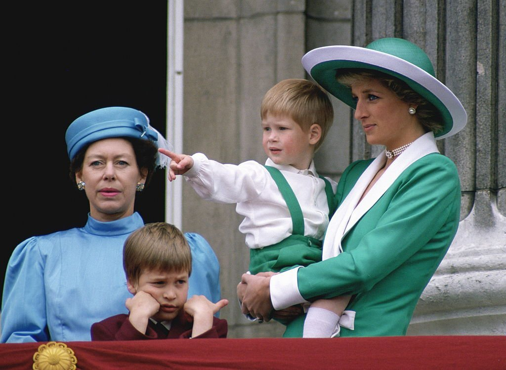 Princess Diana holds Prince Harry in her arms as they stand with Prince William and Princess Margaret from the balcony at Buckingham Palace for the Trooping The Colour on June 11, 1988, England | Source: Tim Graham Photo Library via Getty Images