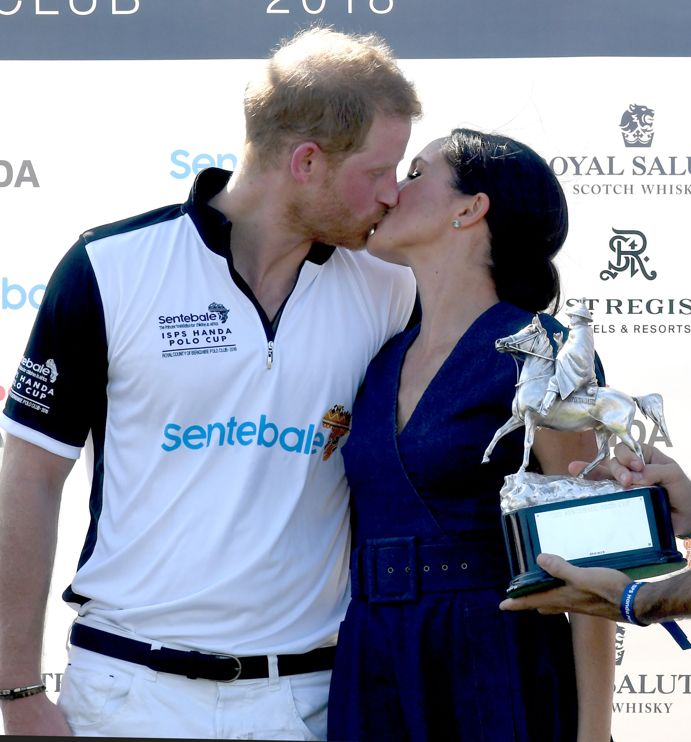 Prince Harry and Duchess Meghan kiss as they pose with the trophy after the Sentebale ISPS Handa Polo on July 26, 2018, in Windsor, England | Photo: Anwar Hussein/WireImage/Getty Images