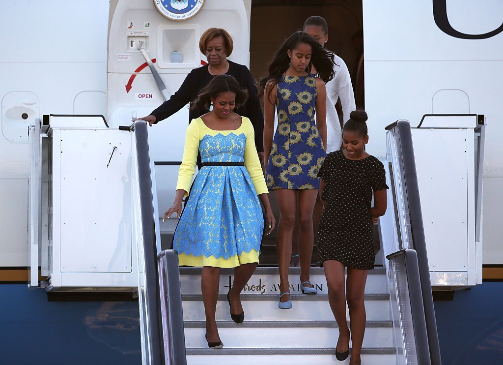 Then First Lady Michelle Obama arriving at Stanstead airport in London with daughters Malia and Sasha Obama and her mother, Marian Robinson on June 15, 2015.
