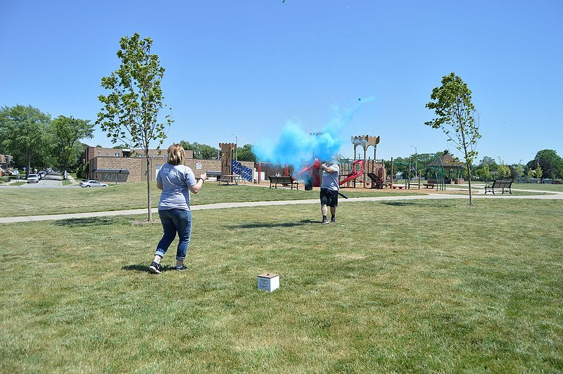 A couple blowing up color smoke crackers during a gender reveal. | Photo: Flickr