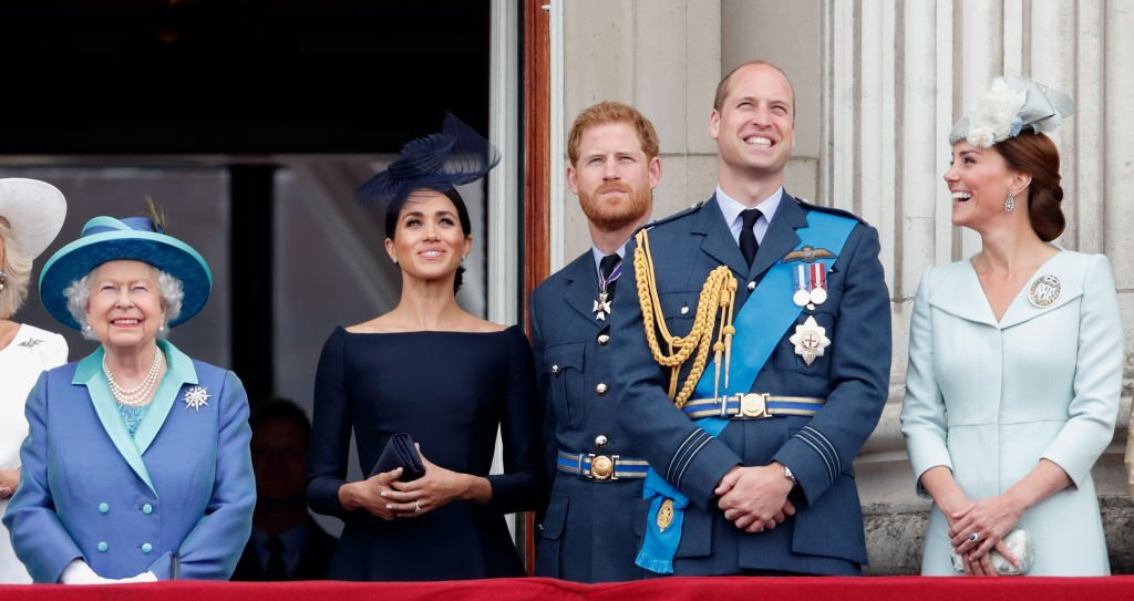 Queen Elizabeth, Meghan Markle, Prince Harry, Prince William, and Prince William stand on the balcony at Buckingham Palace to watch the flypast marking the centenary of the Royal Air Force on July 10, 2018, in London, England | Source: Max Mumby/Indigo/Getty Images