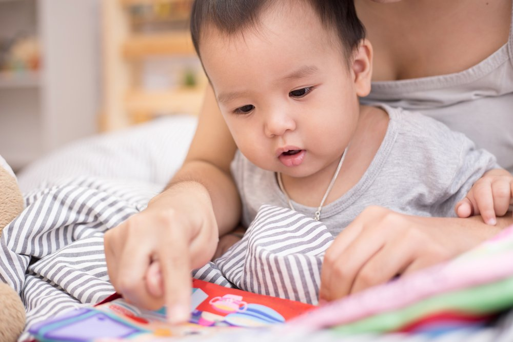 Asian baby looks at book with mom. | Photo: Shutterstock