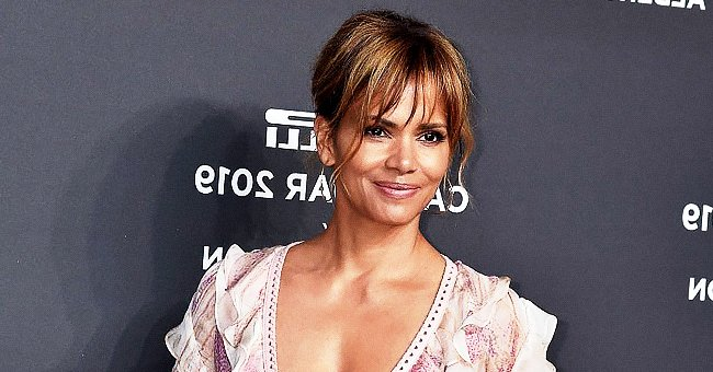 Halle Berry Slays Showing Her Stunning Figure in a Pic Wearing a White Top as She Lays on Sand