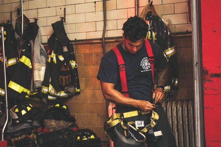 Un pompier qui met sa ceinture. | Photo : Unsplash