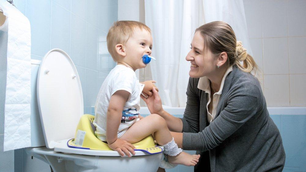 A young mother talking to her toddler son who is using his potty | Photo: Shutterstock