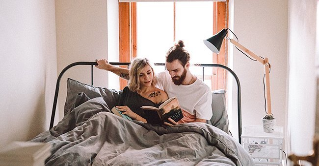 A happy couple reading together in their apartment | Photo: unsplash.com/Toa Heftiba