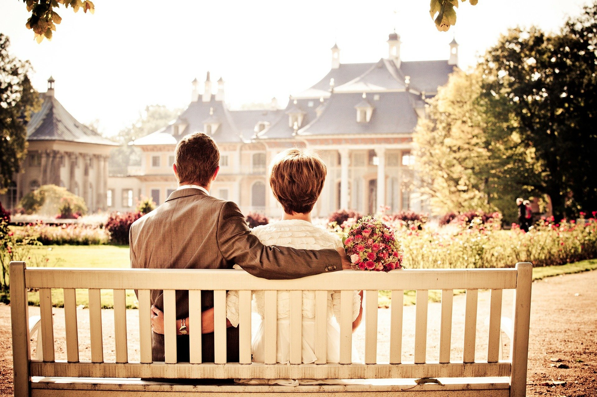 Couple sitting on a bench with their arms wrapped around each other | Source: Pixabay