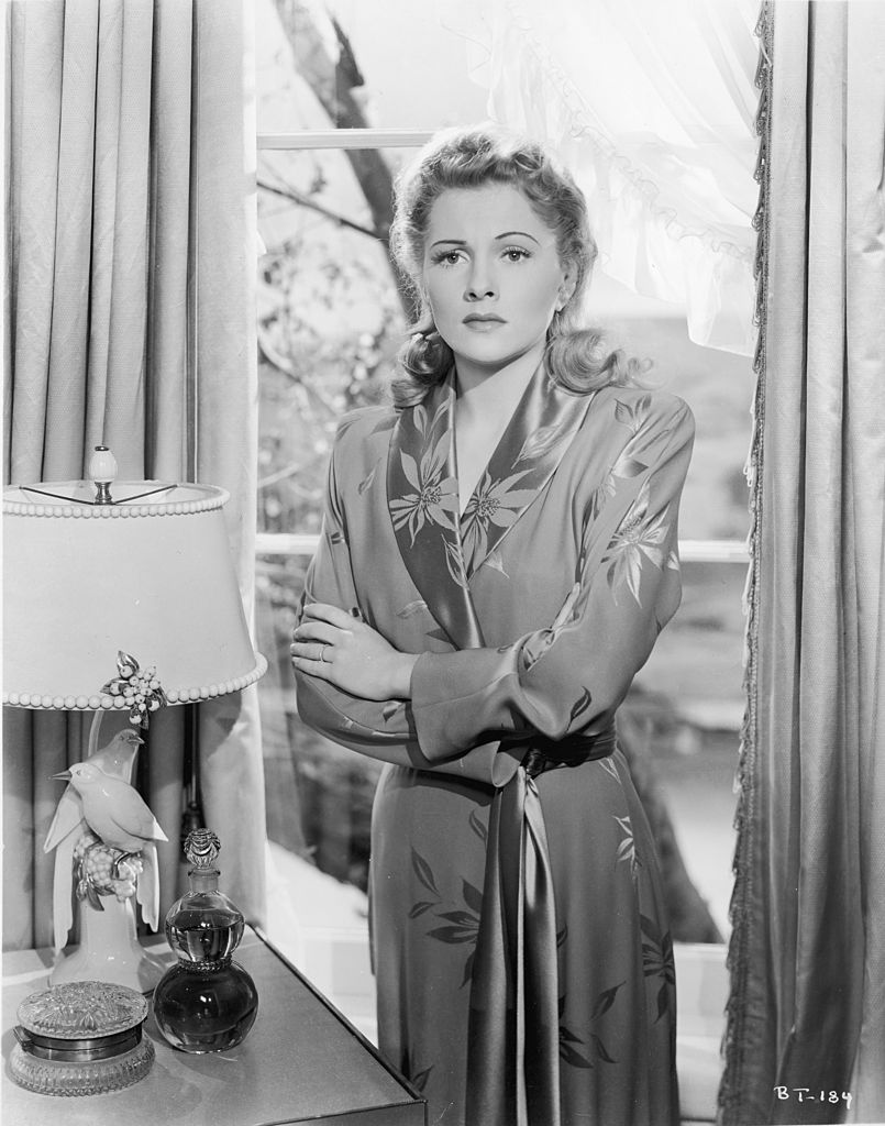 1941: Japanese-born American actor Joan Fontaine stands with her back to a window in a still from the film 'Suspicion,' directed by Alfred Hitchcock. | Source: Getty Images