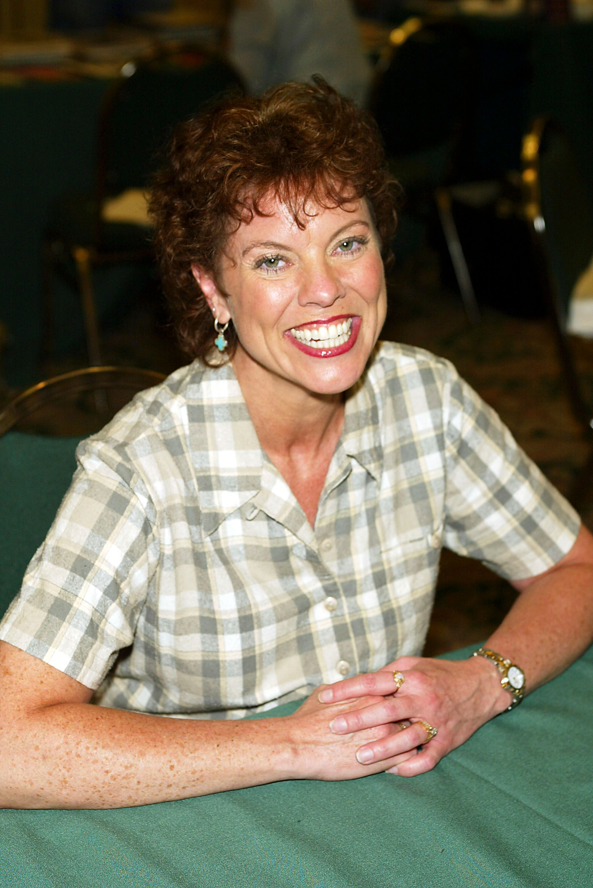 Erin Moran flashes a wide smile as she patiently sits down. | Source: Getty Images