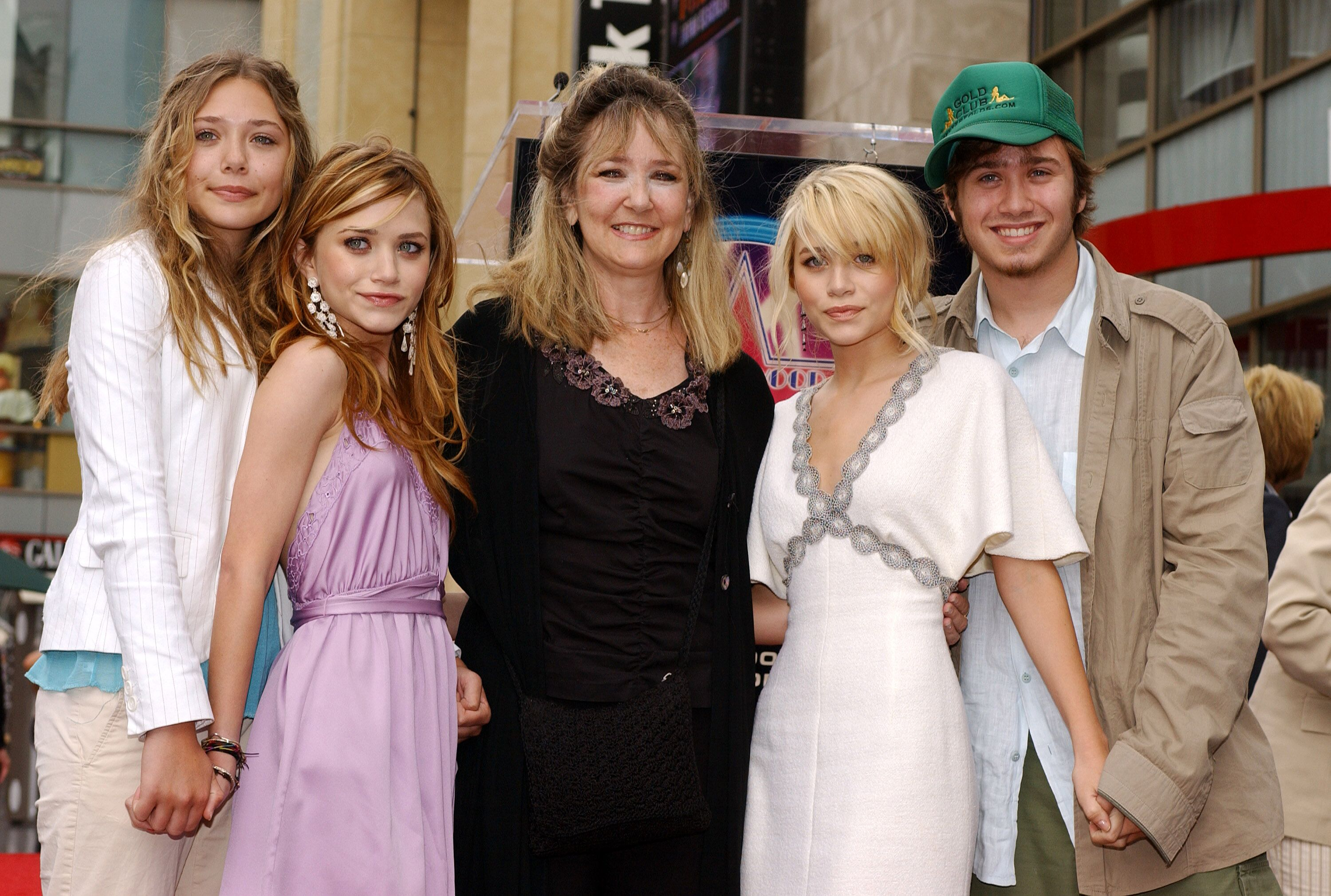 The Olsens -- Elizabeth, Mary-Kate, mother Jarnette, Ashley and brother Trent Olsen -- at the ceremony honoring Ashley and Mary-Kate with a star on the Hollywood Walk of Fame in 2004 | Source: Getty Images