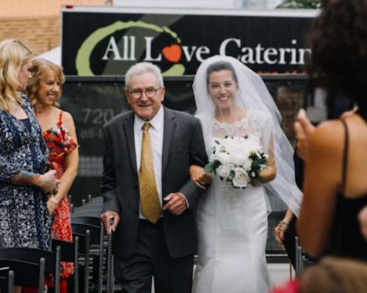 Jim Stamp marchant sa fille Gina dans l'allée à son mariage. | YouTube/GMA
