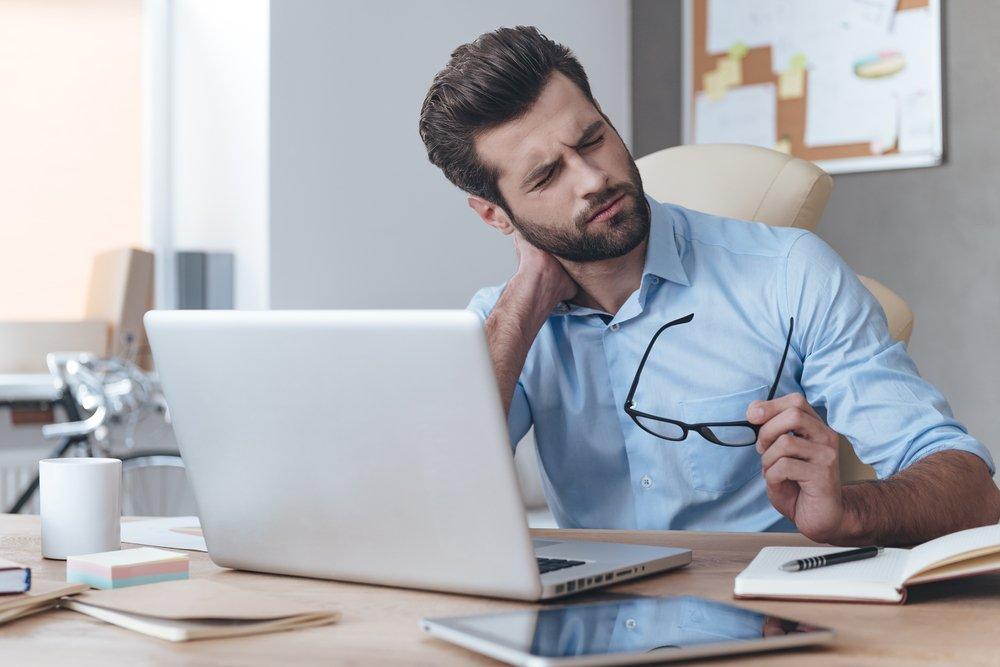 Hombre en oficina con dolor de cuello. Fuente: Shutterstock