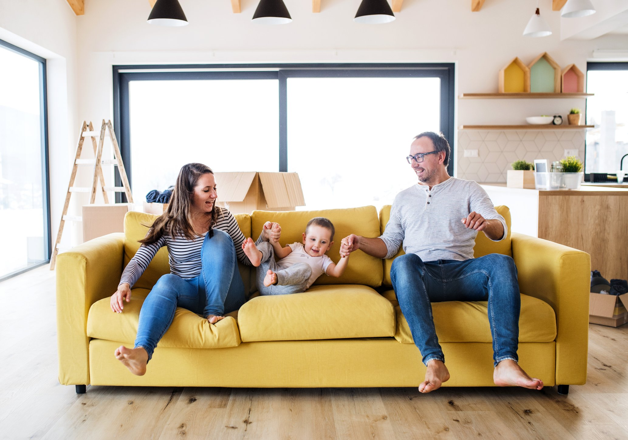 Young family and toddler boy with boxes moving in a new home, having fun on a sofa.   Photo: Getty Images