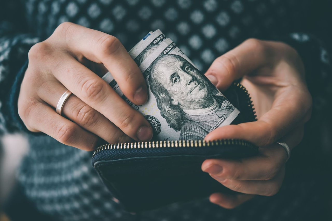 A man taking out a few dollars from his wallet. | Source: Shutterstock