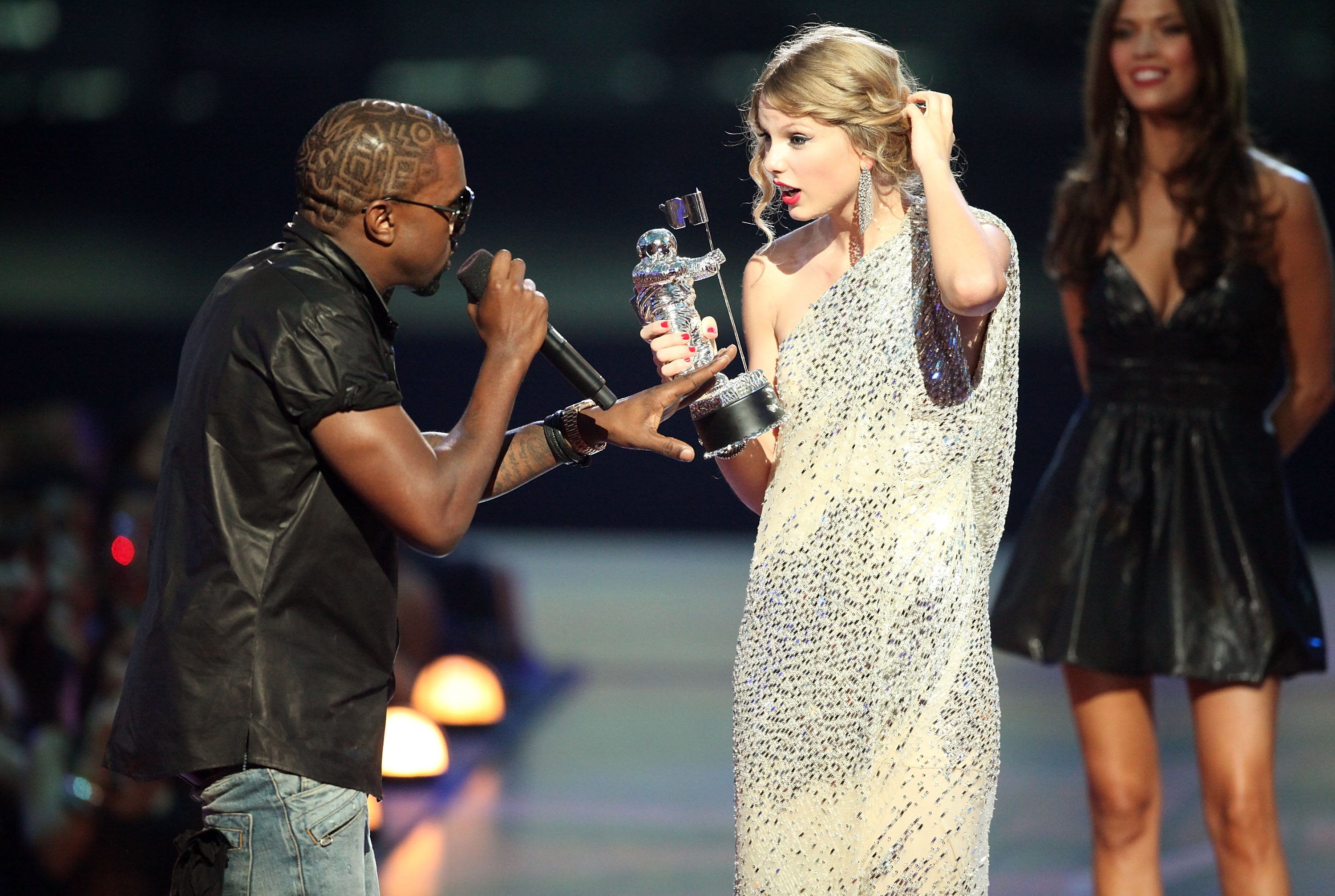 """Kanye West (L) jumps onstage after Taylor Swift (C) won the """"Best Female Video"""" award during the 2009 MTV Video Music Awards at Radio City Music Hall on September 13, 2009, in New York City. 