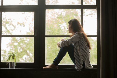 A woman thoughtfully looking out of the window. | Source: Shutterstock.