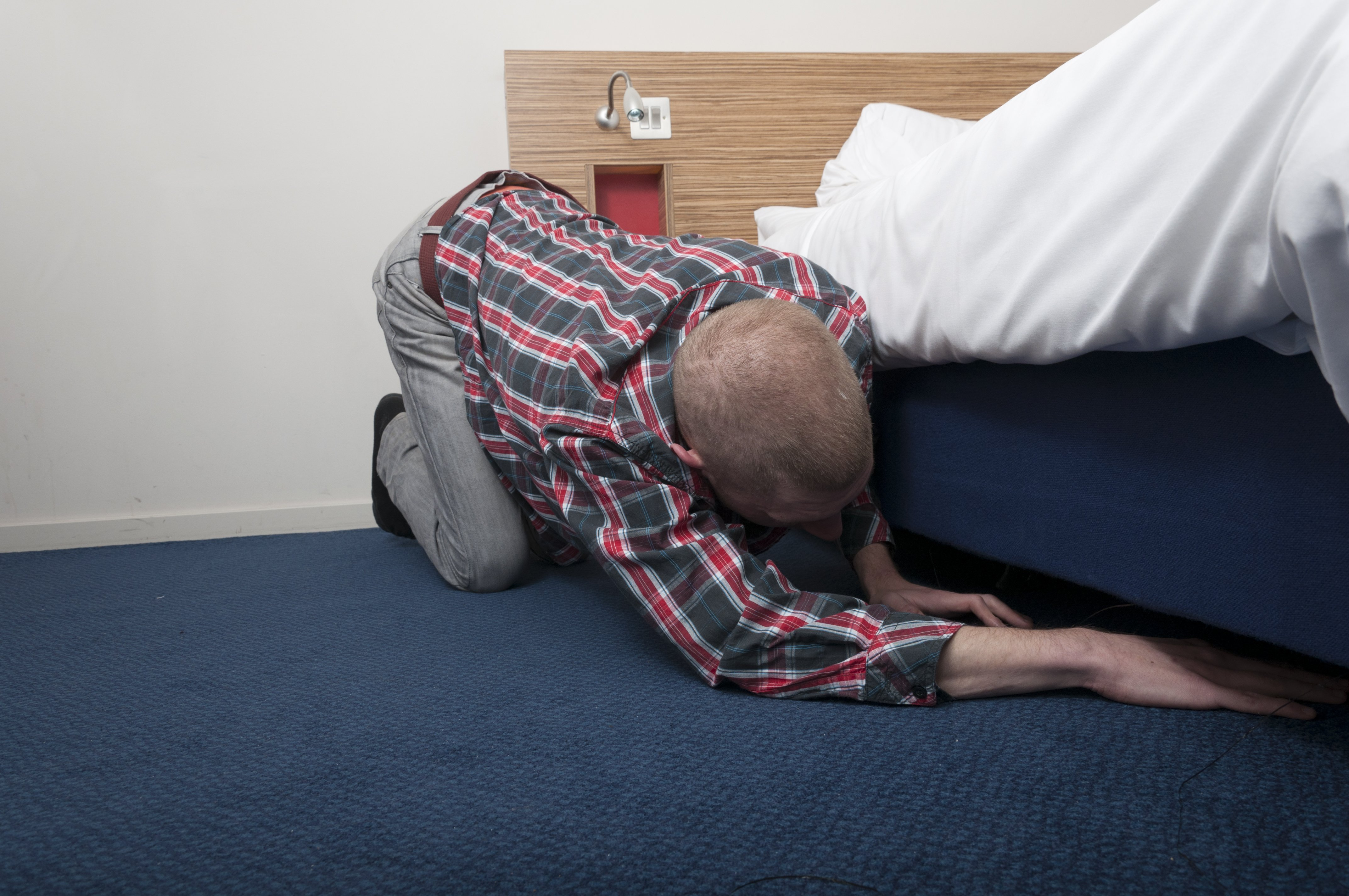 Man looking under the bed. Image credit: Shutterstock