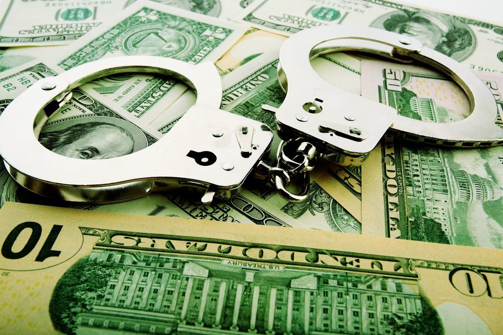 Silver handcuff and dollar bank notes. | Photo: Shutterstock