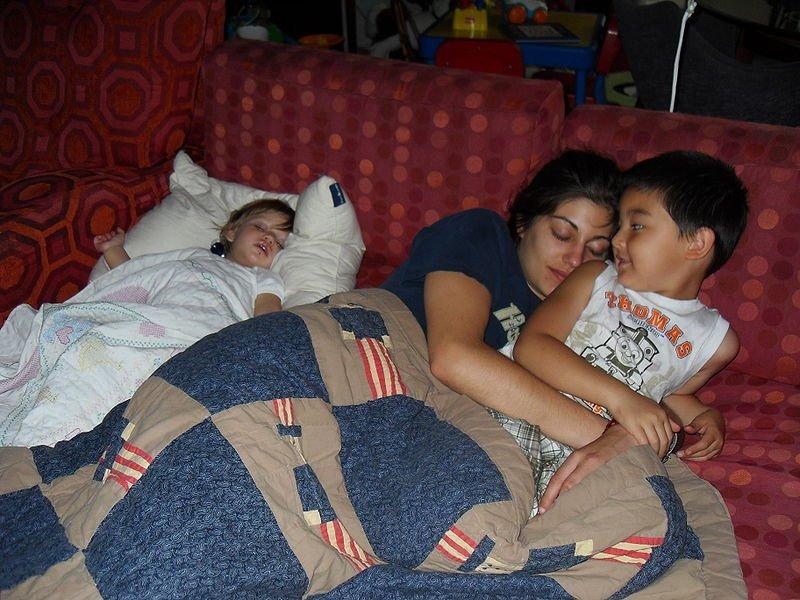 Madre junto a sus dos hijos recostados en un sofá. | Imagen: Wikimedia Commons