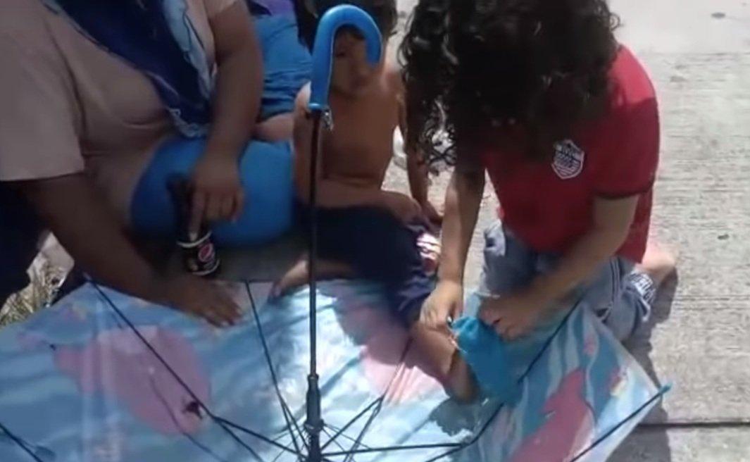Cheikh le coloca sus medias a un pequeño sin hogar   Foto: YouTube/Sahouli Cheikh Faizal