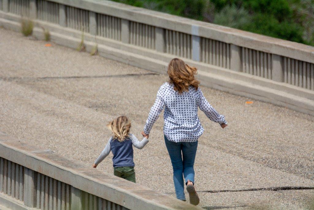 Mujer y una niña caminando por una carretera. | Imagen: Flickr