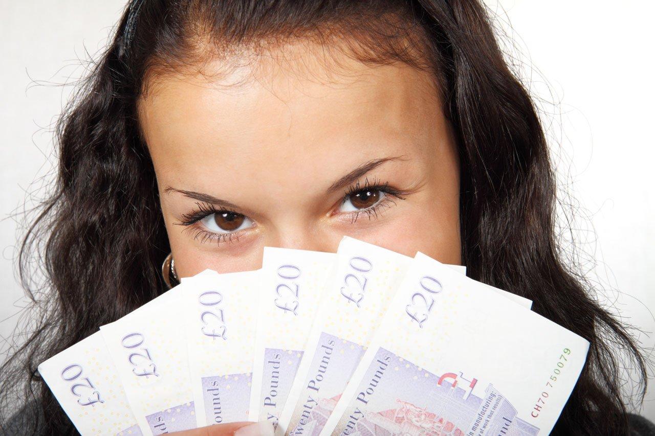 Mujer sosteniendo un puñado de billetes en forma de abanico que cubren su rostro. | Imagen: Public Domain Pictures