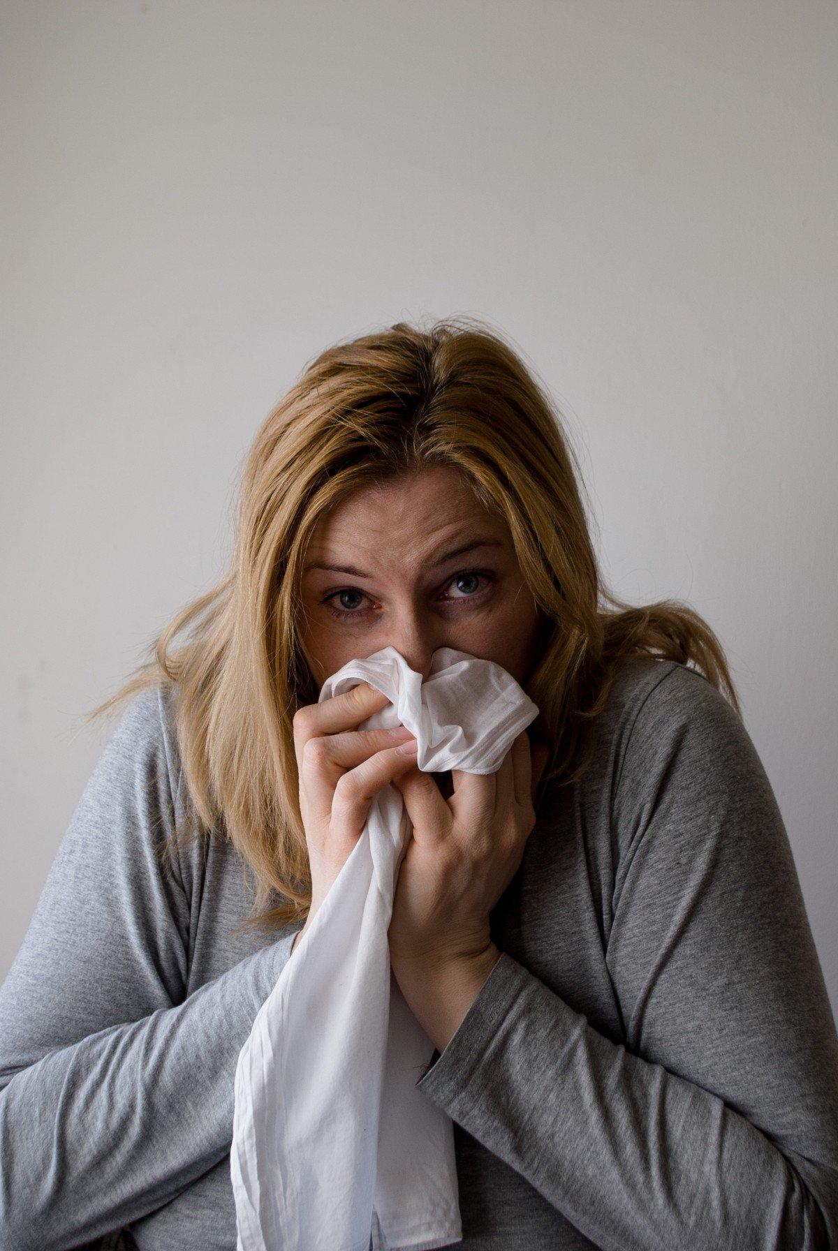 Mujer tosiendo con pañuelo sobre su rostro. | Imagen: PxHere