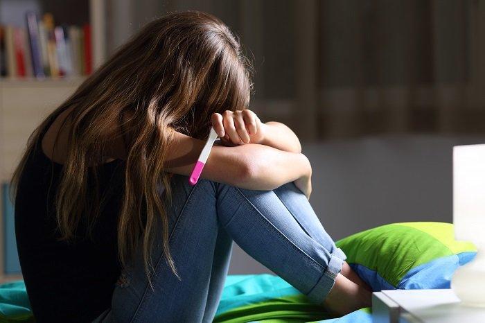 Vista lateral de una adolescente embarazada triste sentada en su cama después de revisar una prueba de embarazo | Foto: Shutterstock.com