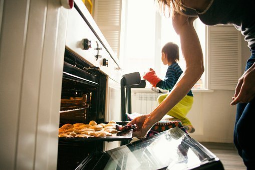 Mother and son baking cookies in kitchen | Photo: Getty Images