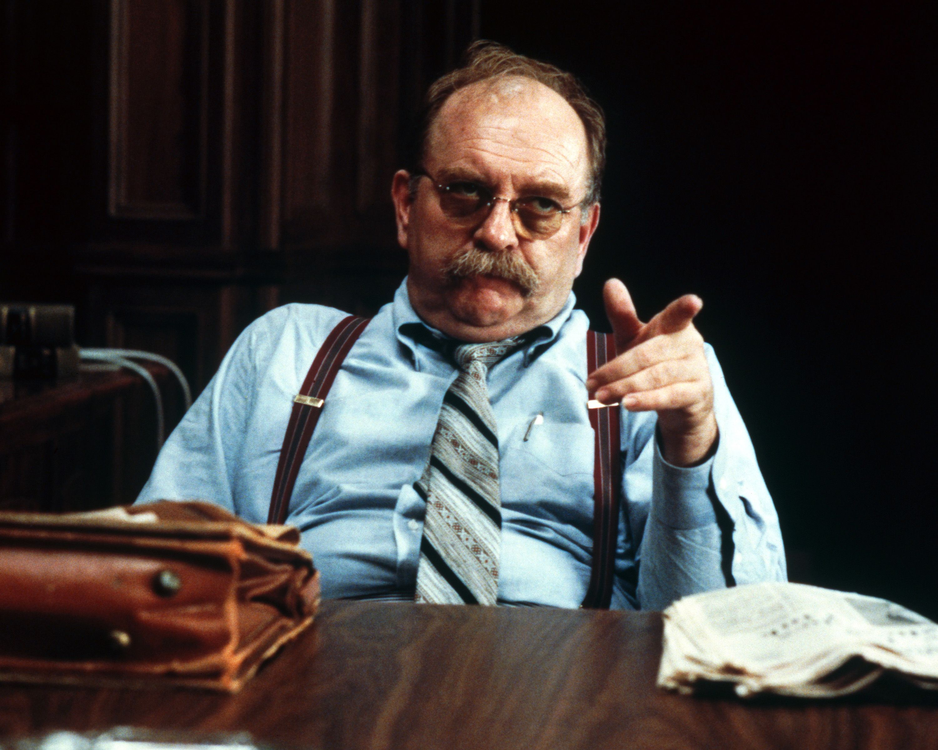 "Actor Wilford Brimley sitting behind a desk during a scene from Sydney Pollack's ""Absence of Malice"" in 1981 