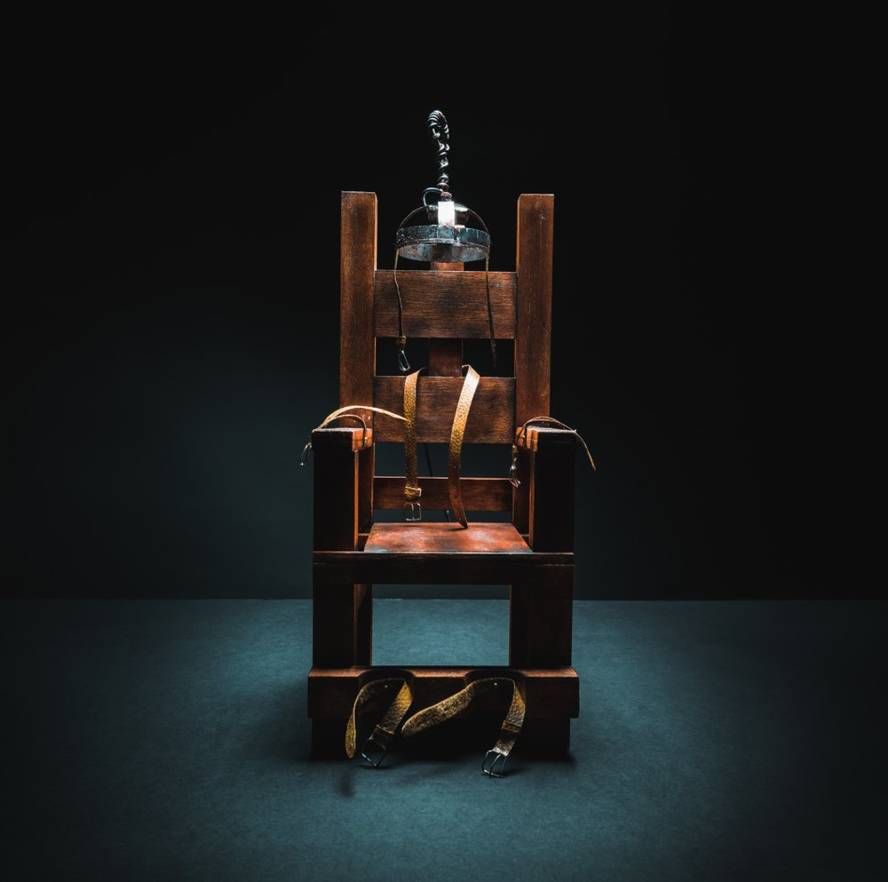 An image of an electric chair scale model on a dark background. | Photo: Shutterstock