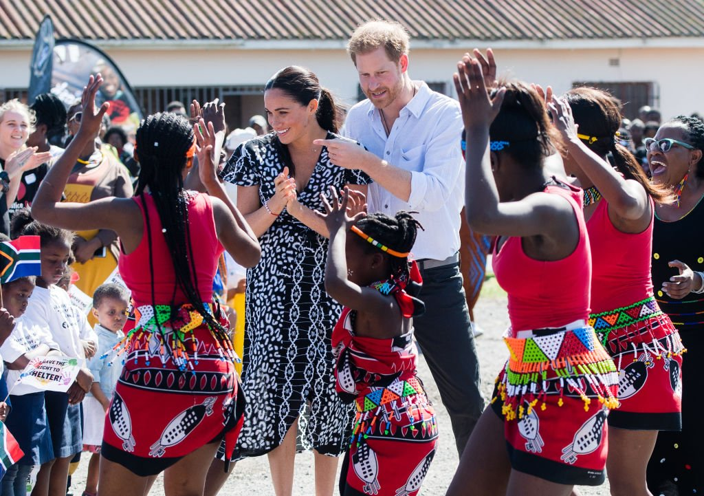 """Prince Harry, Duke of Sussex and Meghan, Duchess of Sussex dance as they arrive for a visit to the """"Justice desk"""", an NGO in the township of Nyanga in Cape Town, as they begin their tour of the region on September 23, 2019. 