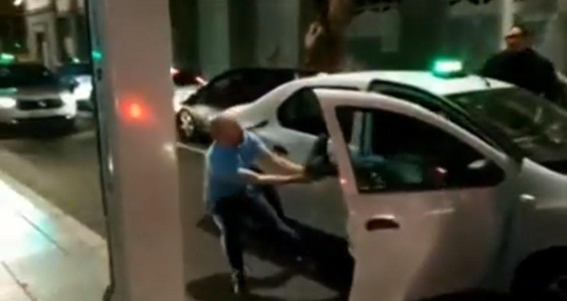 El taxista enfurecido intenta sacar del vehículo al pasajero de manera violenta. Fuente: Facebook / Max Gomez