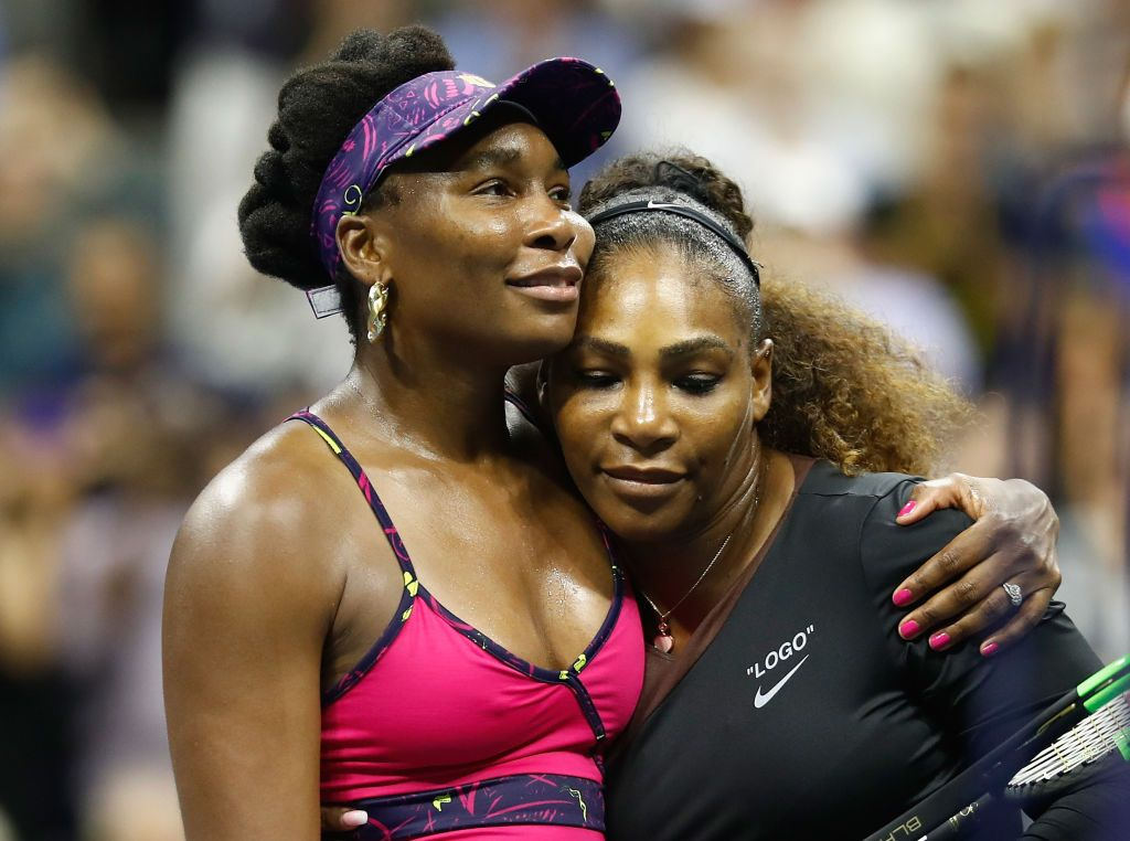 Serena and Venus Williams share a hug at one of their tennis tournaments | Source: Getty Images/GlobalImagesUkraine