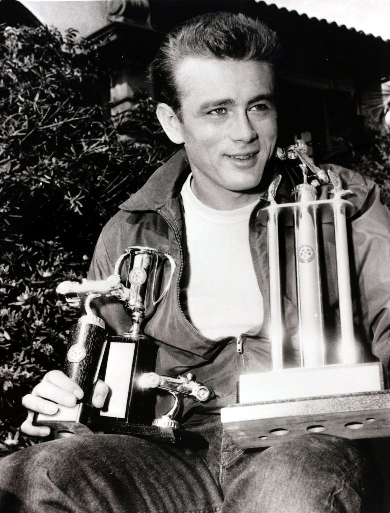 James Dean holding the three trophies he won in the Palm Springs Road Race in May 1955 | Source: Getty Images