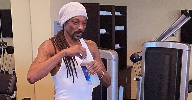 Snoop Dogg Shows off His Muscles Posing in a Gym Wearing a White T-Shirt & Sneakers