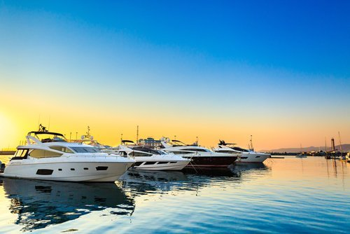Luxury yachts docked at sea port at sunset. | Source: Shutterstock.