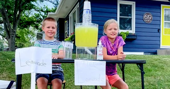 Twins sit and smile at their lemonade stand despite thief that stole all of their tips   Photo: Facebook/karensmidt