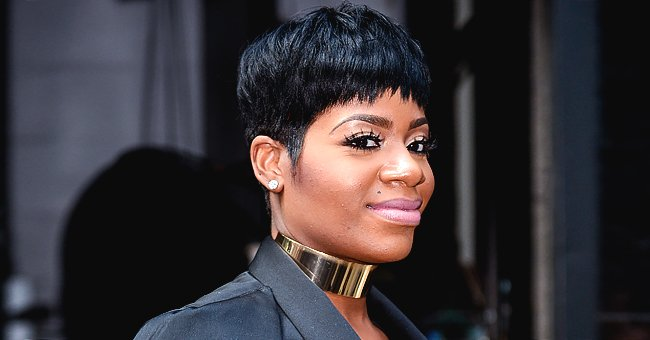 Fantasia Flaunts Snatched Waist & Chest Tattoo as She Poses in Black Top & Tight Jeans in a Photo